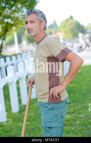 caretaker looking out over army cemetery - Stock Photo