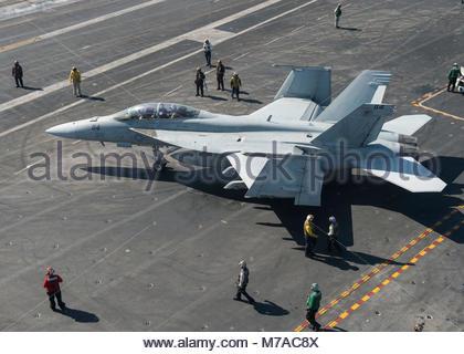 Boeing FA-18F Super Hornet.  ARABIAN GULF (Feb. 27, 2015) Sailors direct an F/A-18F Super Hornet from the Fighting - Stock Photo