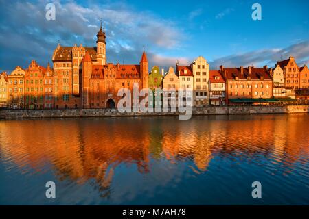 Long Embankment and Motlawa River in the Old Town of Gdansk, Poland at sunrise. Mariacka Gate on the left - Stock Photo