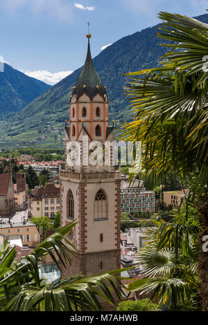 Palms decorate the townscape of Merano with Church of St. Nicholas in South Tirol, seen from the Tappeinerpromenade - Stock Photo