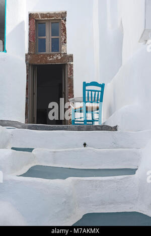 Europe, Greek islands, the Aegean Sea, the Cyclades, Santorini, Imerovigli, blue chair in front of white wall of - Stock Photo