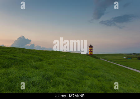 Europe, Germany, the North Sea, Lower Saxony, East Frisia, Pilsum, lighthouse of Pilsum in the evening light - Stock Photo