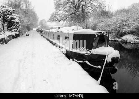 Narrowboats covered in snow are seen moored up on the Llangollen Canal - Stock Photo