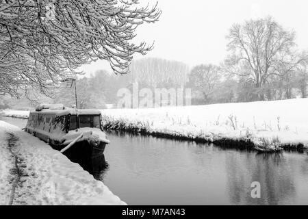 A Narrowboat covered in snow can be seen moored up on the Llangollen Canal - Stock Photo
