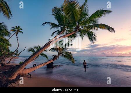 Man on a deserted wild beach at sunrise on the Caribbean island Puerto Rico