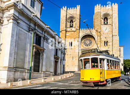 Historic yellow tram in front of the Lisbon Cathedral, Portugal - Stock Photo