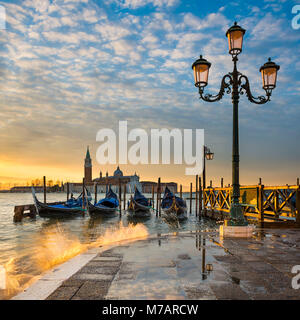 Gondolas on the Grand Canal at sunrise in Venice, Italy - Stock Photo