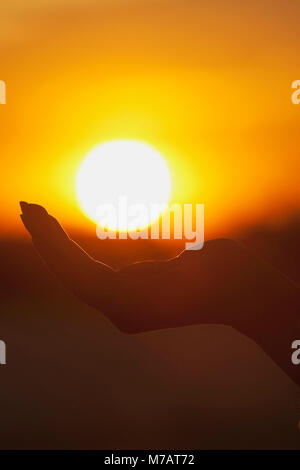 Person cupping hand under sun - Stock Photo