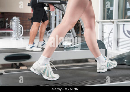 Low section view of a woman and a man walking on treadmills - Stock Photo