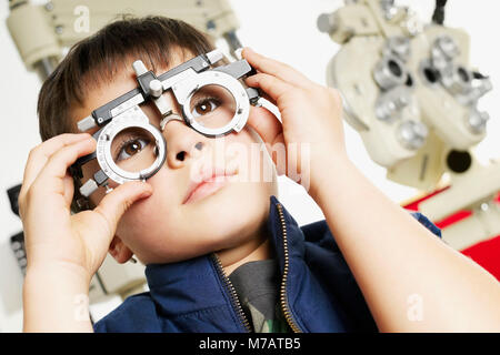 Low angle view of a boy wearing a phoropter in a doctor's office - Stock Photo