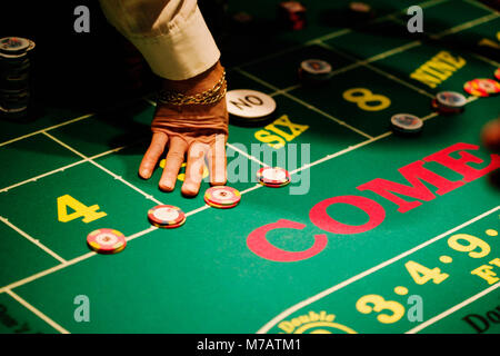 High angle view of a man's hand on a gaming table in a casino, Las Vegas, Nevada, USA - Stock Photo