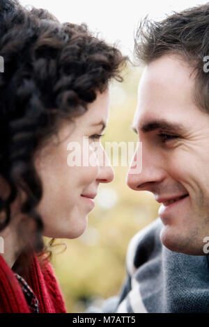 Close-up of a couple looking at each other and smiling - Stock Photo