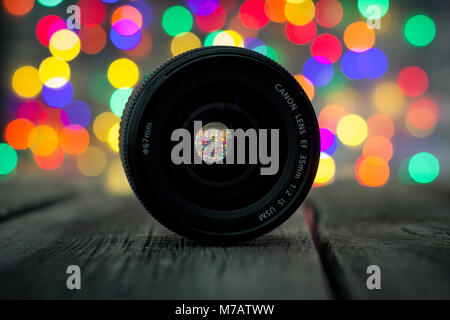 Close-up of the Canon EF 35 mm 1:2 IS USM lens with bokeh Christmas lights in the background - Stock Photo