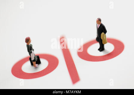 Figurine of a businessman and a businesswoman standing on a percentage sign - Stock Photo