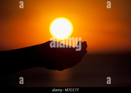 Person's hands cupping under setting sun, Miami Beach, Florida, USA - Stock Photo