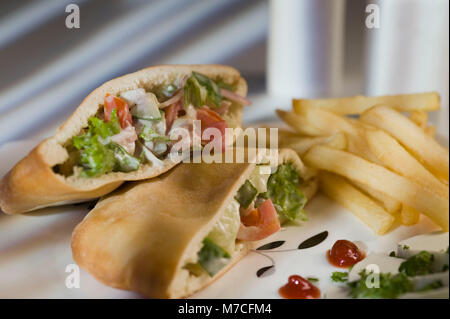 Stuffed pita sandwiches served with French fries - Stock Photo