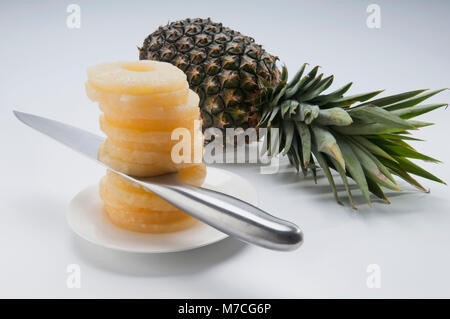 Close-up of a knife in a stack of pineapple slices - Stock Photo