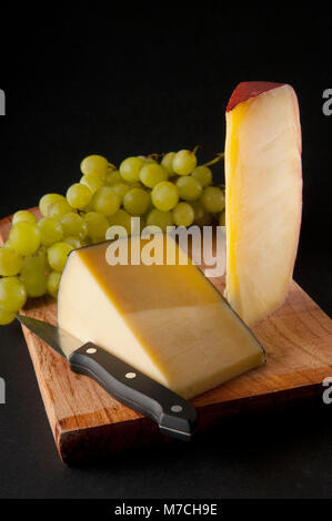 Assorted cheeses and green grapes on a cutting board - Stock Photo