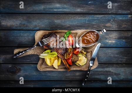 Ribeye steak on bone served with sauce Jack Daniels - Stock Photo