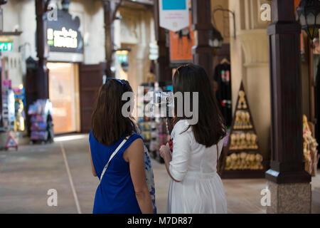 Female tourists taking pictures inside Madinat Jumeirah souk Dubai UAE - Stock Photo