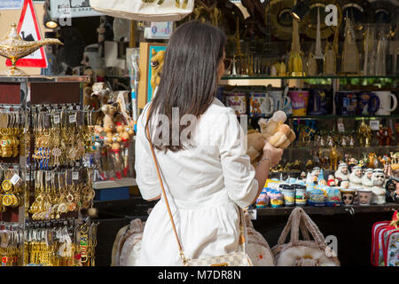 Female tourist buying souvenirs at Souk Madinat Jumeirah Dubai UAE - Stock Photo