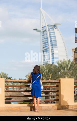 Female tourist looking at Burj Al Arab from Madinat Jumeirah Dubai UAE - Stock Photo