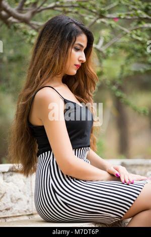 Sad woman sat outdoors looking away