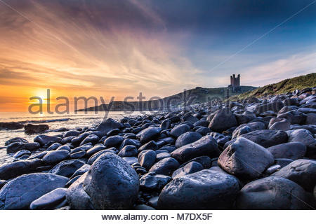 Dunstanburgh castle in Northumberland at dawn. - Stock Photo