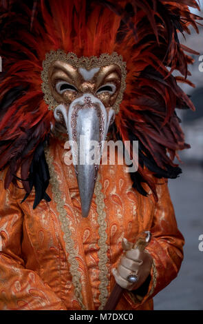 Carnival-goer wearing feathered mask and ornate costume photographed during Venice Carnival / Carnivale di Venezia. - Stock Photo