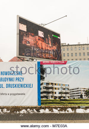 Poznan, Poland - March 07, 2018: New apartment blocks advertisement signs with palace hotel advertisement board - Stock Photo