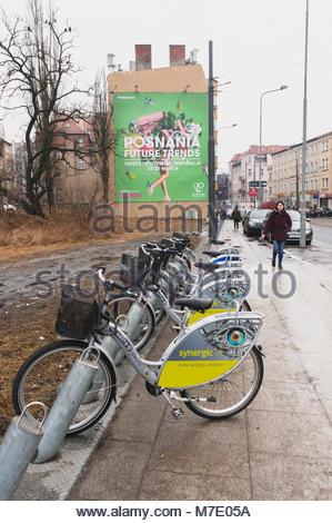 Poznan, Poland - March 07, 2018: Row of rental bicycles with Synergic advertisement board. In the background there - Stock Photo