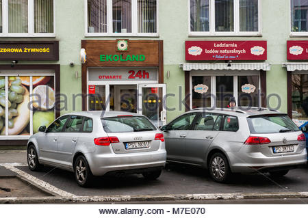 Poznan, Poland - March 07, 2018: Audi and Volkswagen car parked in front of a Ekoland 24h shop and a natural ice - Stock Photo