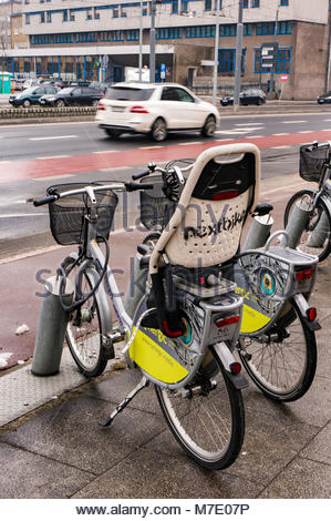 Poznan, Poland - March 07, 2018: Locked rental bicycles with child seat by a road with driving cars in the city - Stock Photo