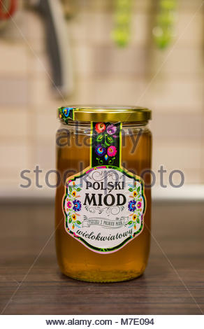 Poznan, Poland - March 07, 2018: Polski Miod flower honey in a glass jar on wooden table - Stock Photo