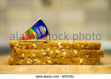 Poznan, Poland - March 07, 2018: Hochland cream cheese with red pepper on a pile of fresh bread in soft focus - Stock Photo