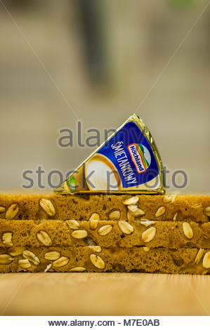Poznan, Poland - March 07, 2018: Packed Hochland cream cheese on fresh slices of bread in soft focus - Stock Photo