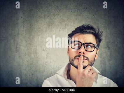 Young handsome man in glasses thinking in doubts and touching lips on gray. - Stock Photo