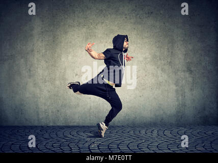 Stylish young man in trendy sportive clothing performing street dance with on gray wall background. - Stock Photo