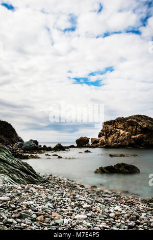 Long exposure, daytime seascape, rocky shore, creamy water, dreamy feeling, empty beach, vertical, white clouds, - Stock Photo
