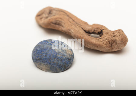 Lapis lazuli  is a deep blue metamorphic rock used as a semi-precious stone on a white background with old wood - Stock Photo