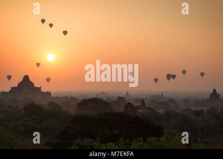 Beautiful view of many hot-air balloons over temples and pagodas at the plain of Bagan in Myanmar (Burma) at sunrise. - Stock Photo