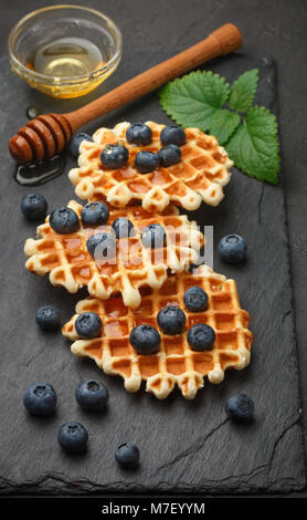 Viennese waffles with honey and fresh berries blueberry and mint on black surface. Delicious dessert - Stock Photo