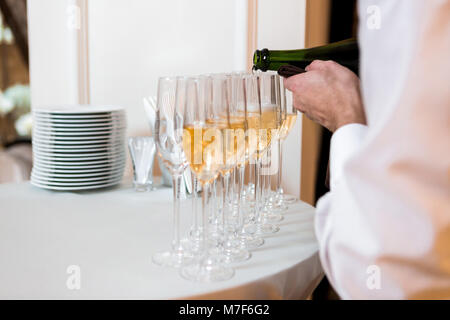 waiter pours champagne. row of glasses at the celebration - Stock Photo