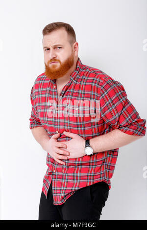 beard man feeling pain, holding his cheek with stomach. Suffering with stomachache - Stock Photo