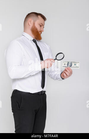 bearded male expert looking at magnifying glass for hundred dollar bill - Stock Photo