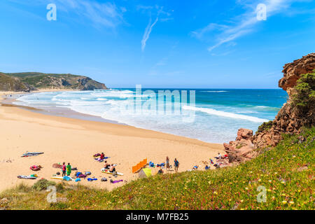 PRAIA DO AMADO BEACH, PORTUGAL - MAY 15, 2015: Surfers relaxing on sandy beach on sunny beautiful day. Water sports - Stock Photo