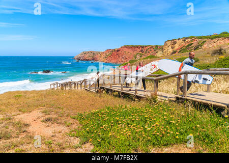 PRAIA DO AMADO BEACH, PORTUGAL - MAY 15, 2015: Surfers with boards walking back from beach on sunny beautiful day. - Stock Photo