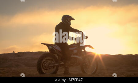 Professional FMX Motorcycle Rider Rests on His Bike and Overlooks Hard Sandy Off-Road Terrain. Sun is Setting. - Stock Photo