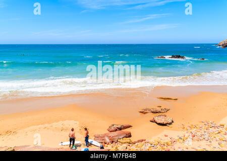 PRAIA DO AMADO BEACH, PORTUGAL - MAY 15, 2015: Surfers relaxing on Praia do Amado beach with ocean waves hitting - Stock Photo