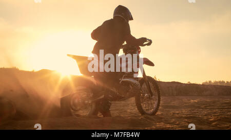 Professional FMX Motorcycle Rider Twists Full Throttle Handle and Starts Riding on the Sandy Off-Road Track. Scenic - Stock Photo